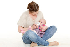 Mother feeding baby from bottle. Young mother feeding baby from bottle on a white background. Happy family Royalty Free Stock Photography