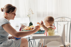 Mother Feeding Baby Boy Stock Images