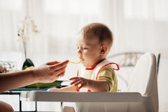 Mother Feeding Baby Boy Stock Photo