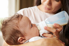 Mother Feeding Baby Boy From Bottle At Home Stock Photo