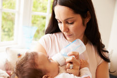 Mother Feeding Baby Boy From Bottle At Home Royalty Free Stock Photos