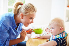 Mother Feeding Baby Boy In High Chair. In Kitchen Stock Images