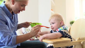 Mother Feeding Baby Boy In High Chair Stock Photography