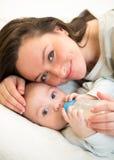 Mother feeding baby boy by milk Royalty Free Stock Photo