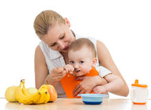 Mother feeding baby boy Stock Image