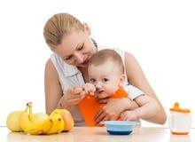 Mother feeding baby boy Stock Image
