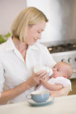 Mother feeding baby with coffee smiling Stock Images