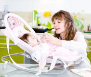 Mother feeding baby with feeding bottle in kitchen Stock Photography