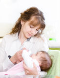 Mother feeding baby with feeding bottle in kitchen Royalty Free Stock Image