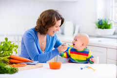 Mother feeding baby first solid food. Mother feeding child. First solid food for young kid. Fresh organic carrot for vegetable lunch. Baby weaning. Mom and Stock Image