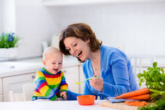 Mother feeding baby first solid food. Mother feeding child. First solid food for young kid. Fresh organic carrot for vegetable lunch. Baby weaning. Mom and Royalty Free Stock Photography