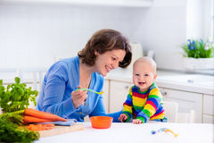 Mother feeding baby first solid food. Mother feeding child. First solid food for young kid. Fresh organic carrot for vegetable lunch. Baby weaning. Mom and Stock Photography
