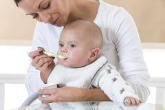 Mother feeding baby food Royalty Free Stock Photos