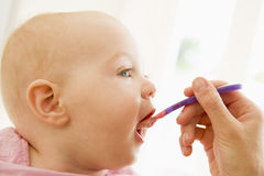 Mother feeding baby food to baby Stock Photo