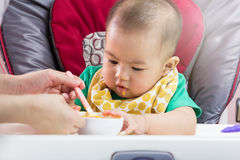 Mother feeding baby food Royalty Free Stock Images