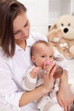 Mother feeding baby girl with bottle stock images