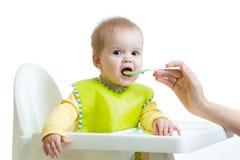 Mother feeding baby girl Stock Photo