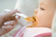 Mother feeding baby girl (9-12 months) with spoon, close-up, side view Stock Photos