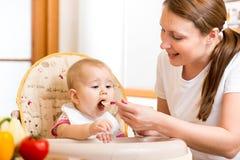 Mother feeding baby girl Stock Image