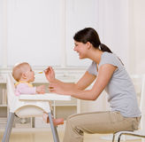 Mother feeding baby in highchair in kitchen