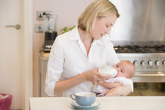 Mother feeding baby in kitchen with coffee Royalty Free Stock Image