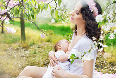 Mother feeding a baby in the orchard Royalty Free Stock Images