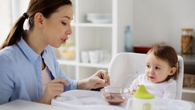 Mother feeding baby with puree at home stock video