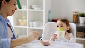 Mother feeding baby with puree at home stock footage