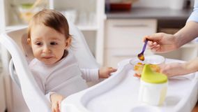 Mother feeding baby with puree at home. Family, food, child, eating and parenthood concept - mother trying to feed little baby with fruit or vegetable mash at stock video