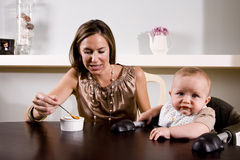 Mother feeding baby sitting in high chair Royalty Free Stock Photography