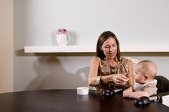 Mother feeding baby sitting in high chair Royalty Free Stock Photos