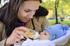 Mother feeding baby son with a bottle in park setting. Mother and her baby royalty free stock photo