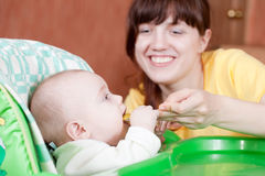 Mother feeding   baby   with spoon Stock Images
