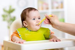Mother feeding baby with spoon Royalty Free Stock Photos
