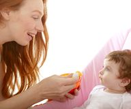 Mother feeding baby yellow spoon Royalty Free Stock Images