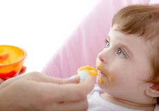 Mother feeding baby yellow spoon Stock Images
