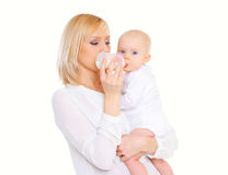 Mother feeding from bottle her baby over white. Background Royalty Free Stock Photography