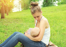 Mother feeding breast baby on the grass in summer. Day Royalty Free Stock Photo