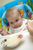 Mother feeding caucasian baby Stock Photos