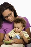 Mother feeding child. African American mid adult mom sitting with toddler son on lap eating cereal