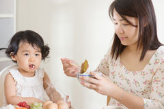 Mother feeding child Stock Photo