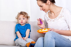 Mother feeding child on couch. Young women feeding her fussy child while sitting on a sofa stock image