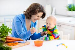 Mother feeding baby first solid food. Mother feeding child. First solid food for young kid. Fresh organic carrot for vegetable lunch. Baby weaning. Mom and Stock Images