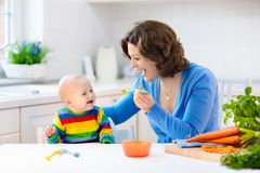 Mother feeding baby first solid food. Mother feeding child. First solid food for young kid. Fresh organic carrot for vegetable lunch. Baby weaning. Mom and Stock Photo
