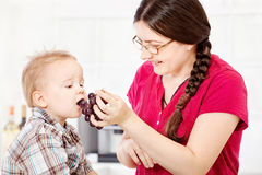Mother feeding child with grape. S in kitchen Stock Photography