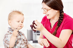 Mother feeding child with grape. Mother feeding son with grapes in kitchen Stock Images