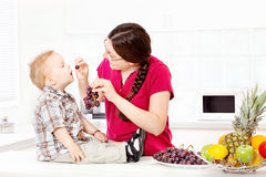 Mother feeding child with grapes. In kitchen Stock Image