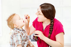 Mother feeding child with grapes. In kitchen Stock Images