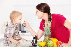 Mother feeding child in kitchen. Mother feeding child with an apple in the kitchen Stock Photography