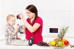 Mother feeding child in kitchen. Mother feeding child with grapes in kitchen Stock Image
